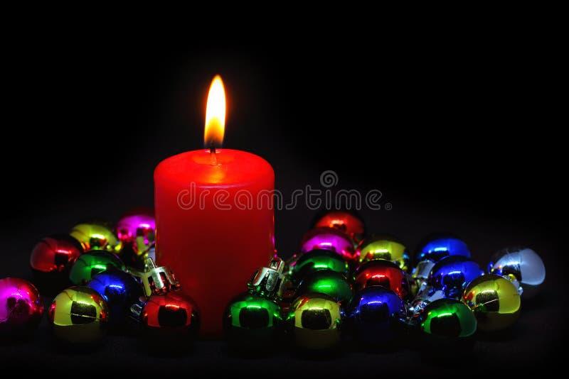 与小圣诞节球的红色蜡烛在黑色 免版税库存图片