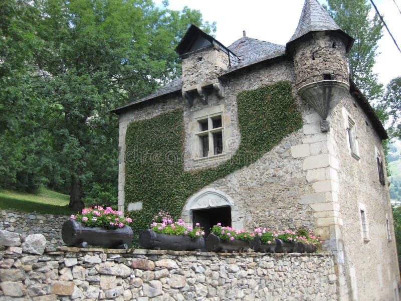 与小塔楼和花的石豪宅在花床上 免版税库存图片