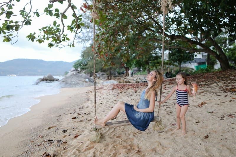 与小女儿的年轻母亲骑马摇摆海滩、海和沙子的在背景中 库存图片