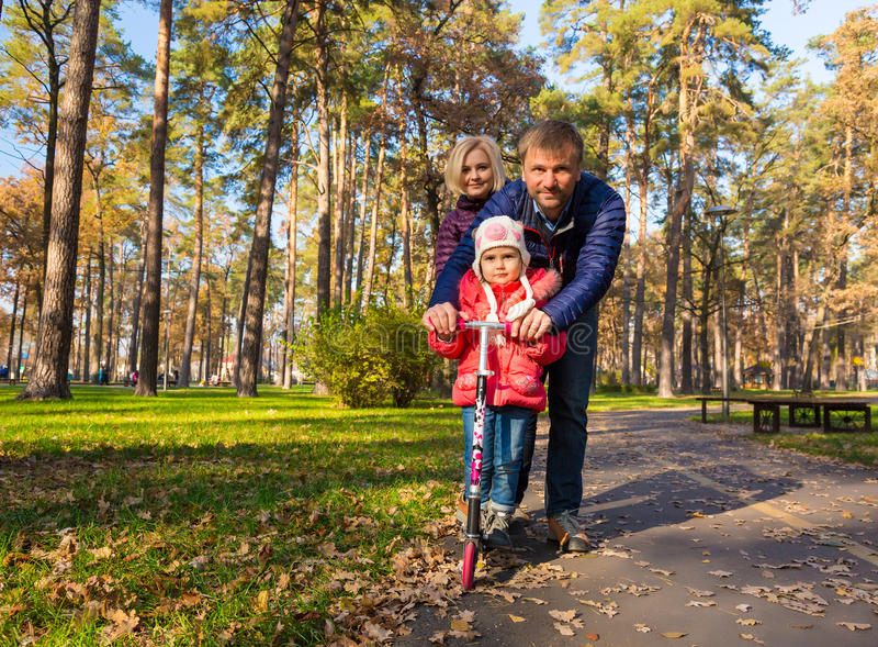 与小女儿的愉快的家庭步行的在公园 图库摄影