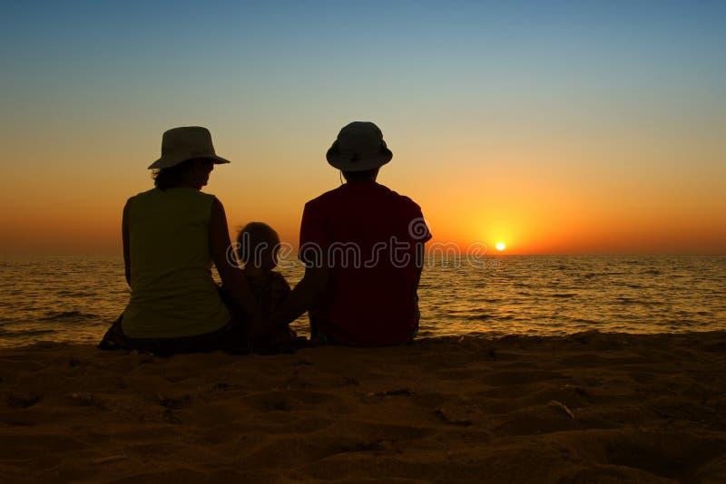 与小婴孩的家庭一起坐日落海滩 家庭 免版税库存照片