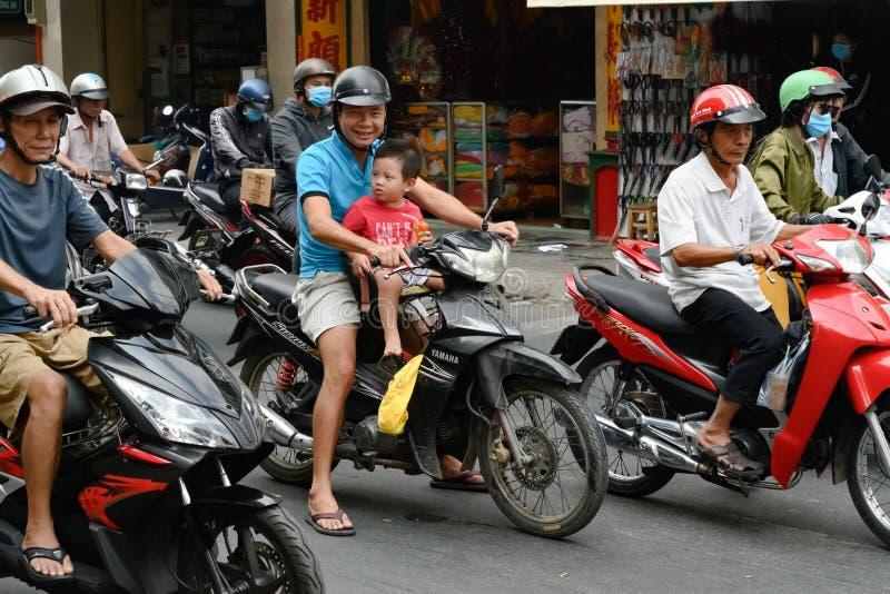 与小孩的摩托车车手Ho池氏Mingh市,以前西贡,越南街道的  免版税库存图片