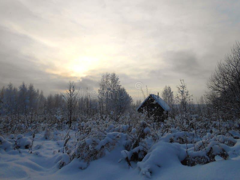 与小屋的冬天风景多雪的领域的 免版税库存照片