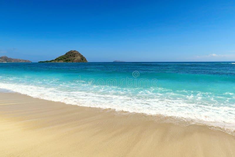 与小山的理想的白色清楚的沙子海洋海滩在天际在松巴哇岛海岛,印度尼西亚 图库摄影