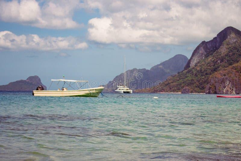 与小岛和白色小船前景的热带海滩 与游艇和小船的海景在海岛背景 库存照片