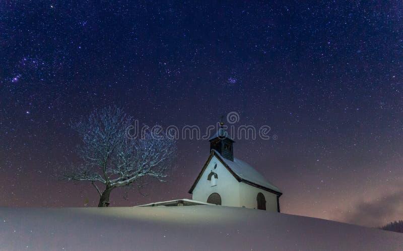 与小教堂的意想不到的stary冬天夜 库存照片