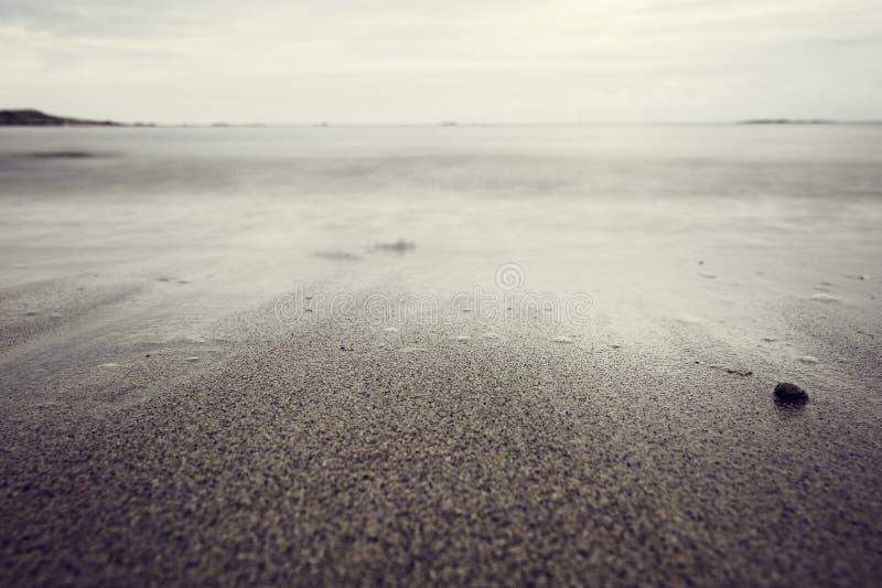 与小束的波浪的沙滩 库存照片