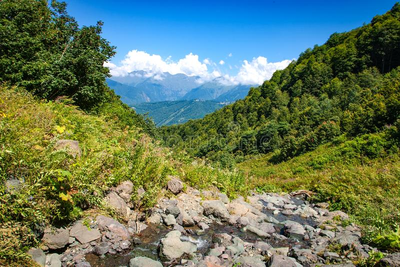 与小河和山的高加索山脉风景在背景中冠上 免版税库存图片
