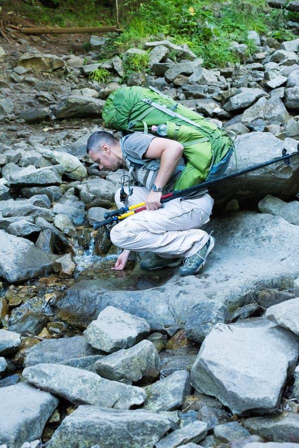 与小河的远足者饮用水 库存照片