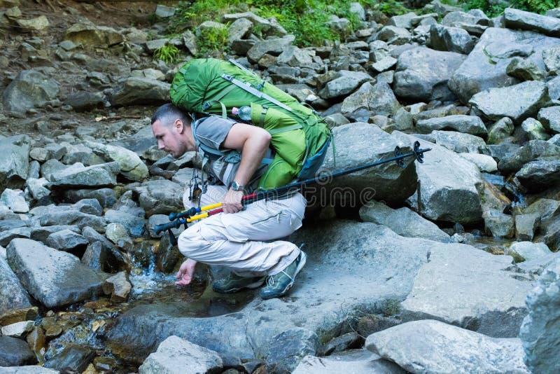 与小河的远足者饮用水 库存图片
