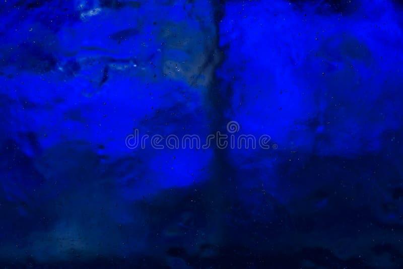 与小泡影的清楚的透明冰 深刻的蓝色光 免版税图库摄影