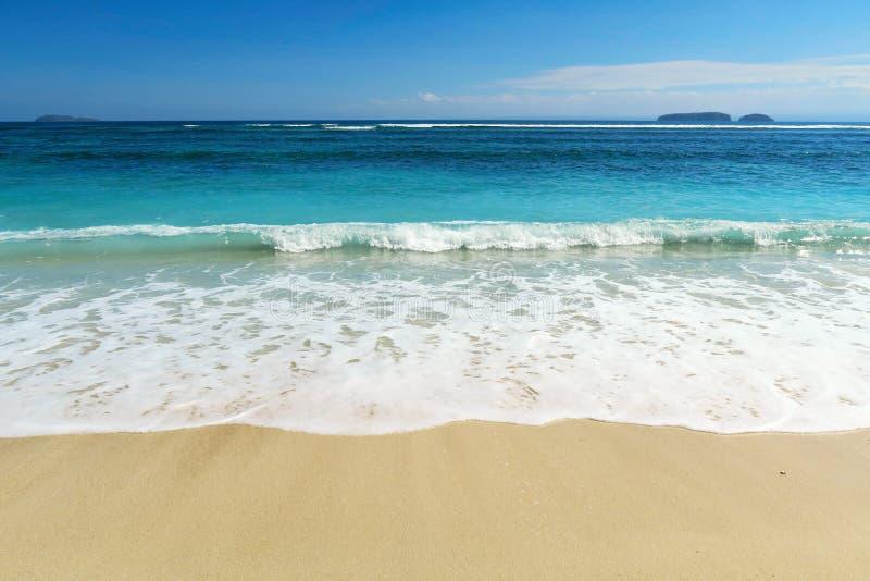 与小波浪和泡沫的理想的白色清楚的沙子海洋海滩 免版税图库摄影