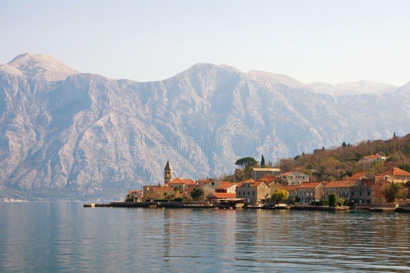 与小海滨村庄的美好的地中海风景在山的背景中 黑山,科托尔湾 图库摄影