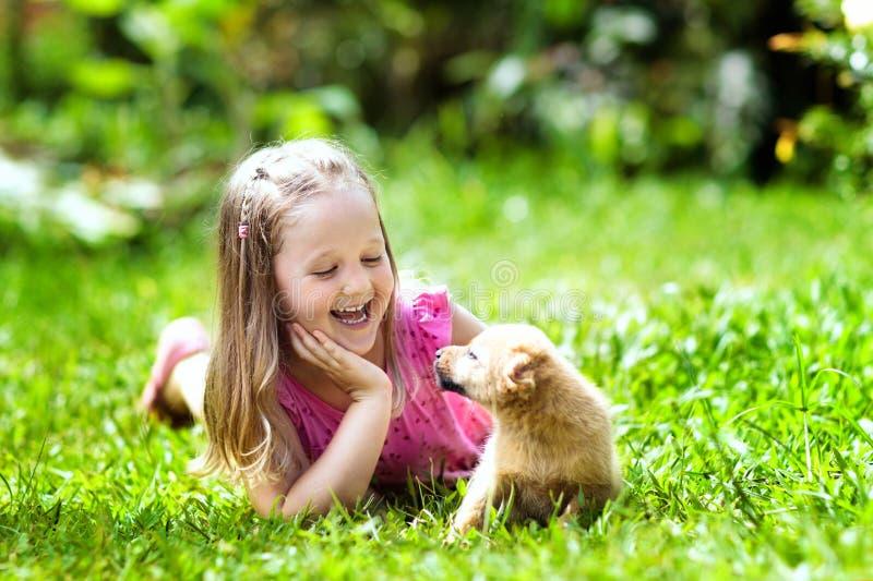 与小狗的孩子戏剧 孩子和狗在庭院里 库存图片