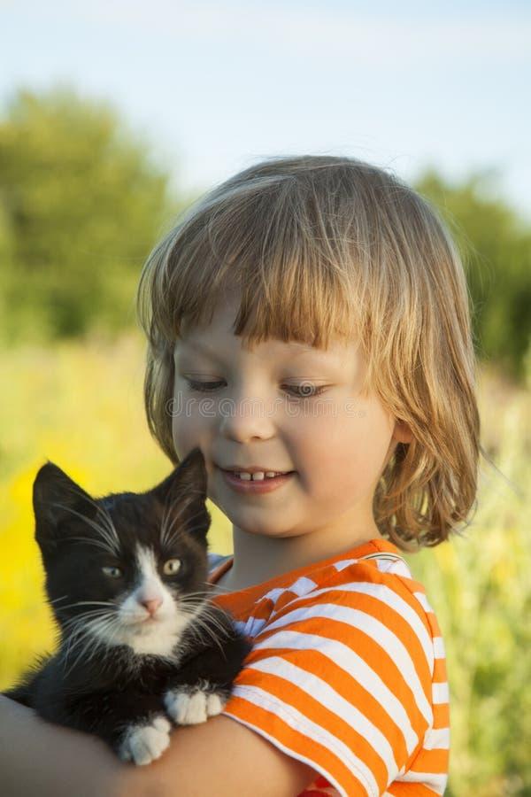与小猫的愉快的孩子 免版税图库摄影