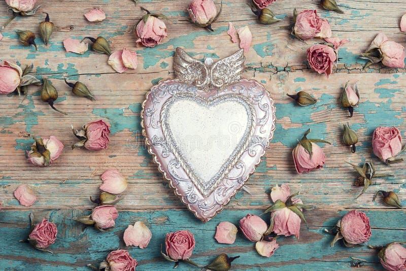 与小玫瑰色花的装饰心脏在绿松石老wo 免版税库存图片