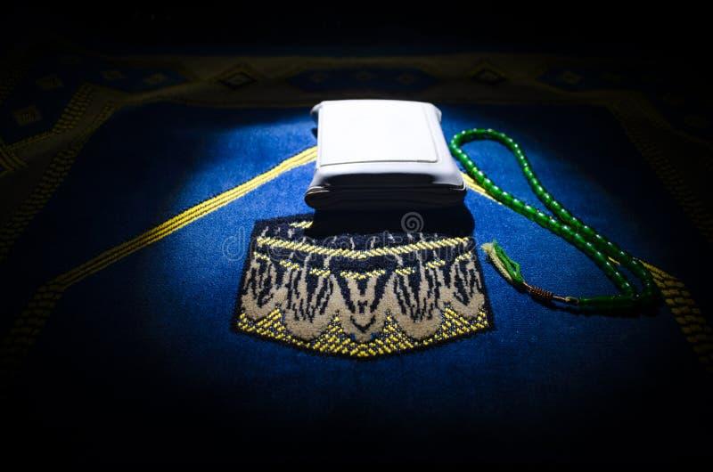 与小珠在跪垫,穆斯林Tasbih的圣洁古兰经是与一起由穆斯林传统上使用念珠的串  图库摄影