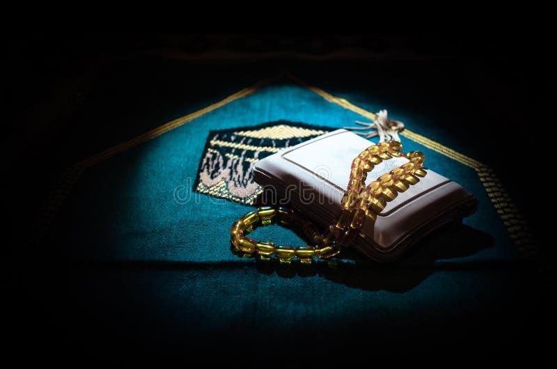 与小珠在跪垫,穆斯林Tasbih的圣洁古兰经是与一起由穆斯林传统上使用念珠的串  免版税库存图片
