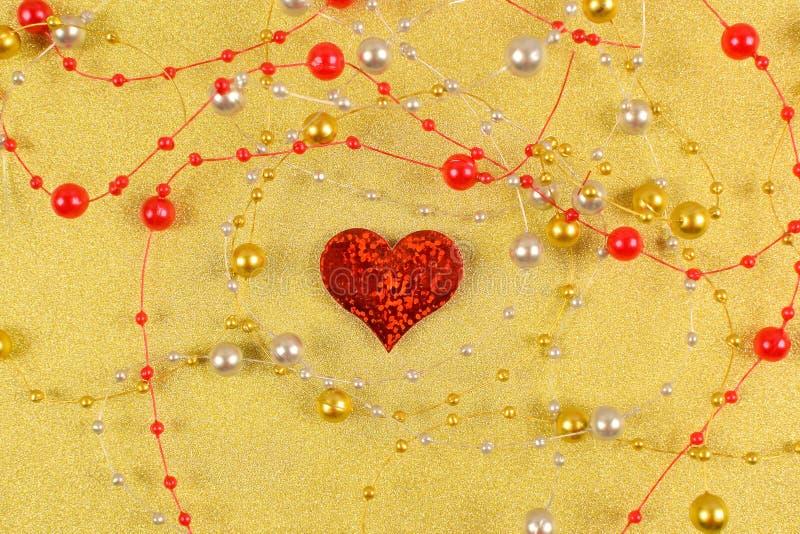 与小珠的红心在金背景 库存图片