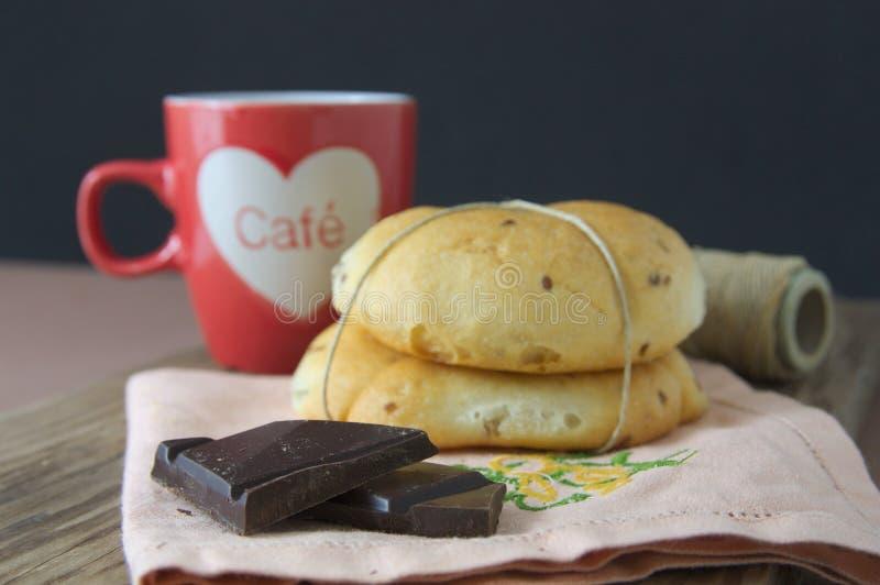 与小甜面包和咖啡的巧克力在桌上 免版税库存照片