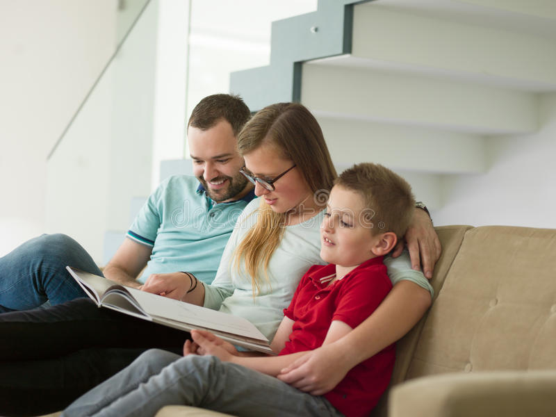 与小男孩的家庭在现代客厅享用 库存图片