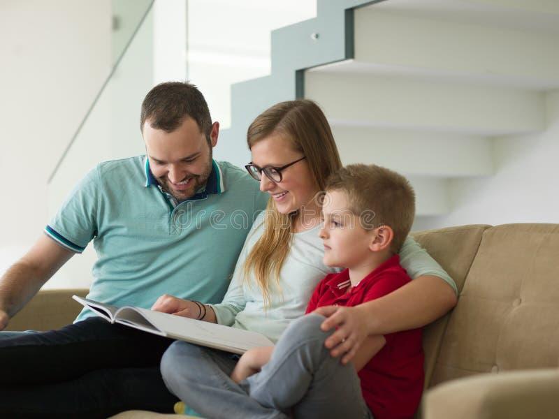 与小男孩的家庭在现代客厅享用 图库摄影