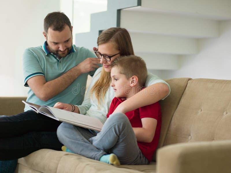 与小男孩的家庭在现代客厅享用 免版税库存图片