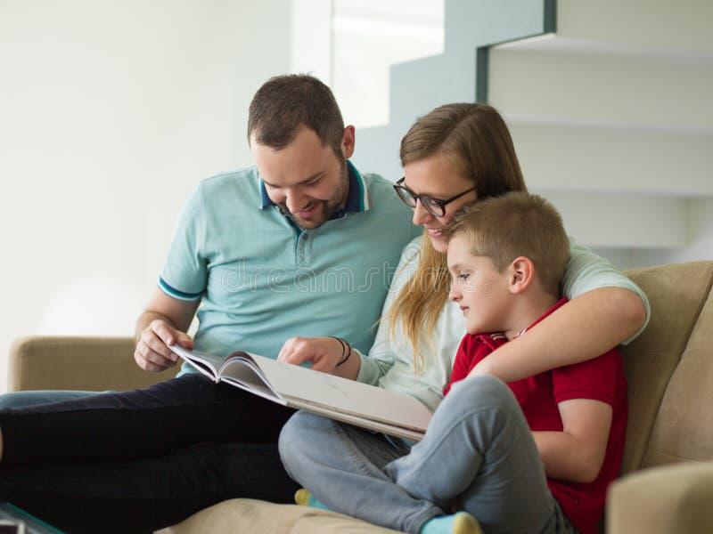 与小男孩的家庭在现代客厅享用 免版税图库摄影