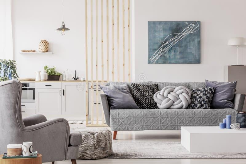 与小白色厨房和客厅的开放单室公寓有灰色长沙发和木咖啡桌的 图库摄影