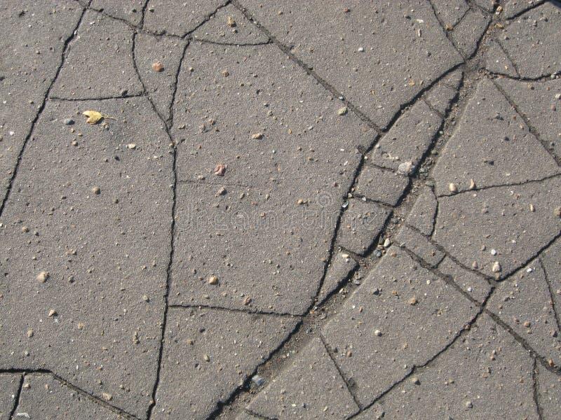 与小石头的破裂的灰色沥青纹理 免版税库存照片