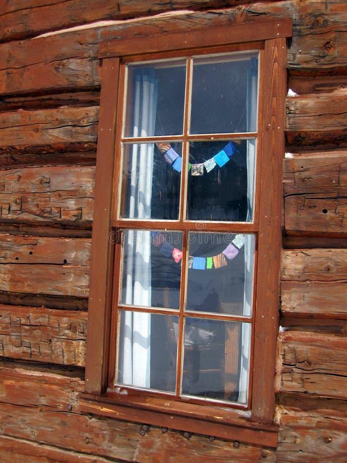 与小祷告旗子的原木小屋窗口 免版税库存照片