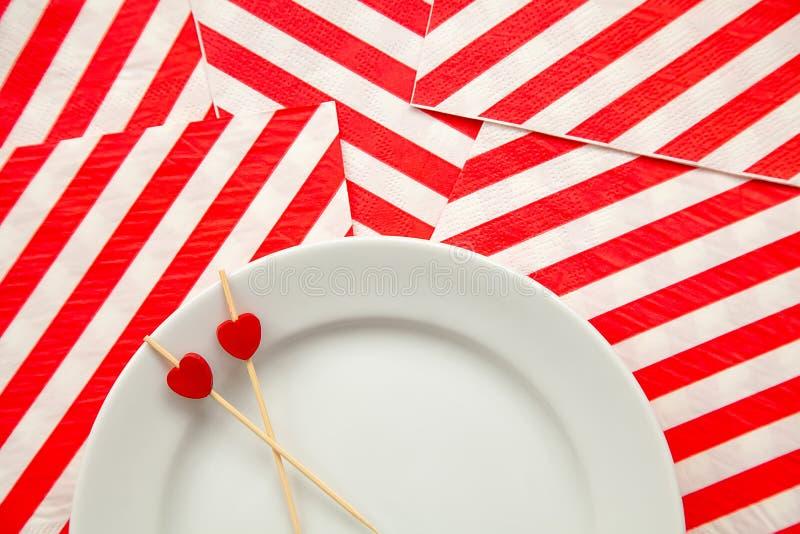 与小红心的两根牙签在一块白色板材和和镶边假日餐巾上背景  免版税库存图片