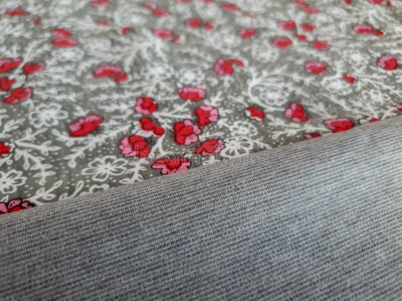 与小红色花的葡萄酒花卉织品在灰色背景 库存图片