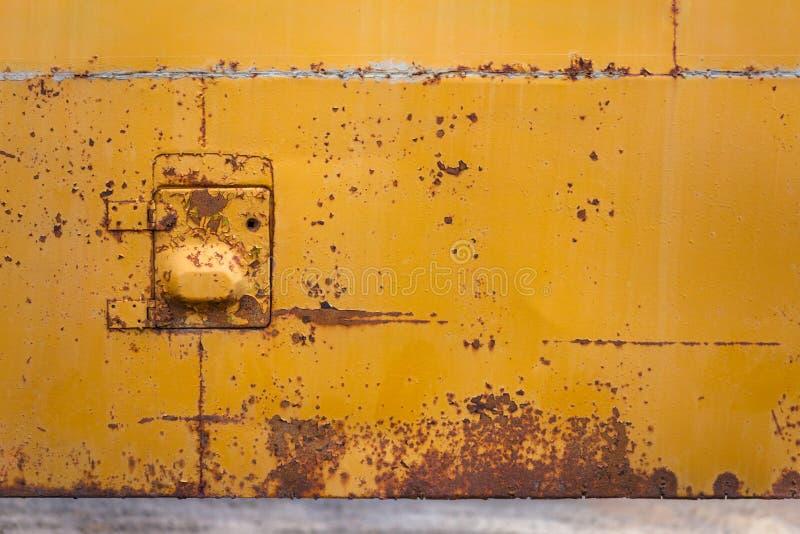 与小舱口盖的生锈的黄色公共汽车板 免版税库存照片