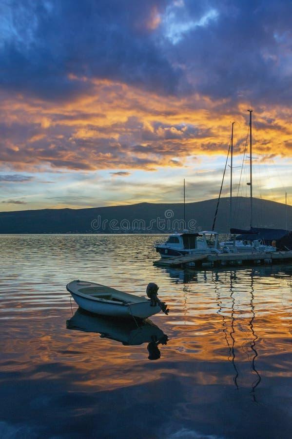 与小船剪影的美丽如画的地中海日落在水的 黑山,科托尔湾 图库摄影