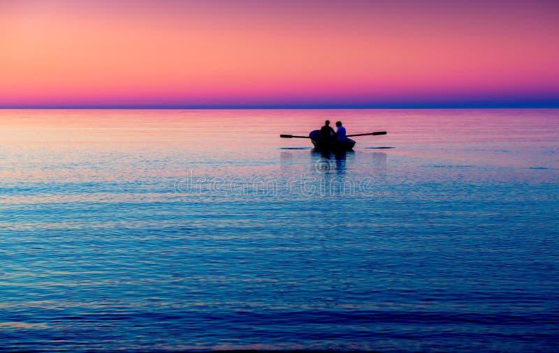 与小船的海景在紫色 免版税库存图片
