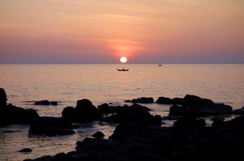 与小船的红色金黄海洋日落从岩石岸 免版税库存照片