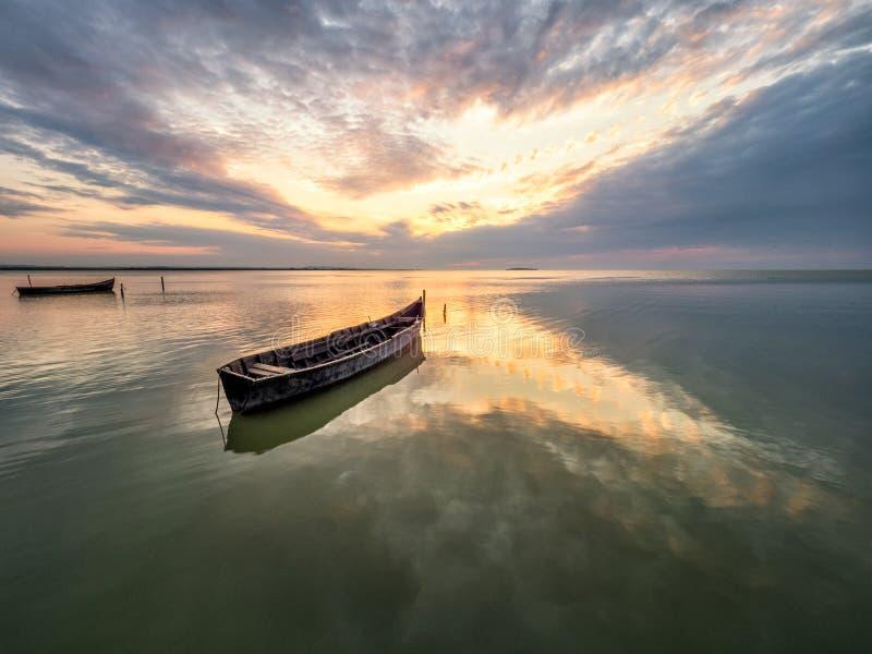 与小船的美好的早晨风景在日出的湖 免版税库存图片