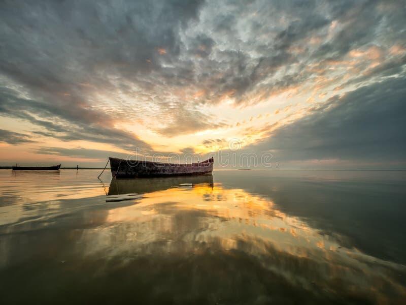与小船的美好的早晨风景在日出的湖 免版税库存照片