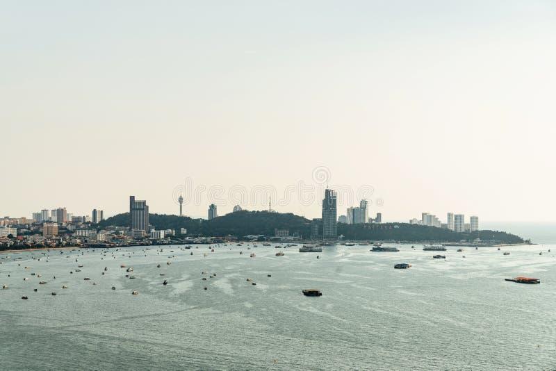 与小船的都市风景全景与建筑大厦的和海景,芭达亚海滩明亮的天空在Chon Buri,泰国 库存照片
