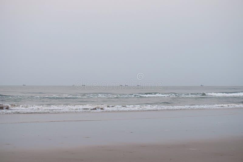 与小船的镇静海滩在天际, Aareware, Ganpatipule,马哈拉施特拉,印度 免版税库存照片