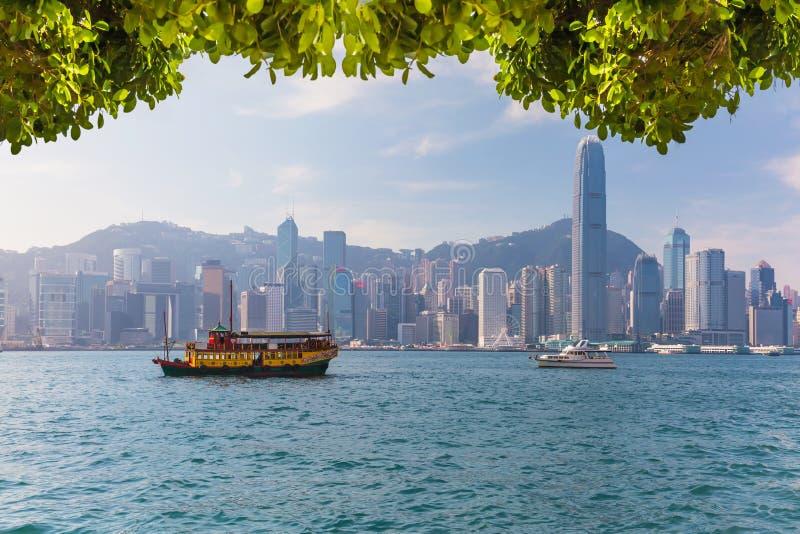 与小船的香港地平线在维多利亚港口 库存照片