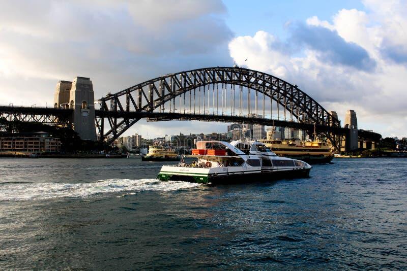 与小船通过的悉尼港桥视图 库存照片