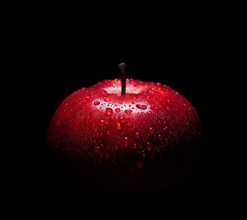 与小滴的新鲜的红色苹果反对黑背景的水 免版税库存照片