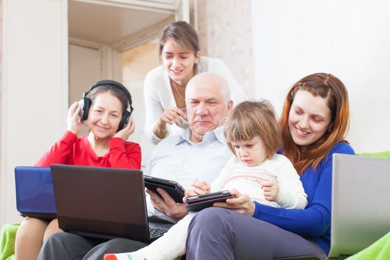 与少量设备一起的愉快的家庭在家 免版税图库摄影