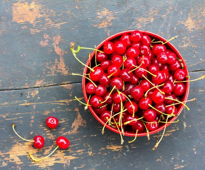 与尾巴的红色成熟樱桃在老黑木背景的一块圆板材与裂缝 库存照片