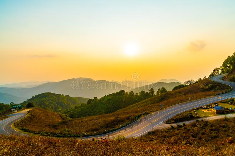 与层数山和路的美丽的日落天空 免版税库存图片