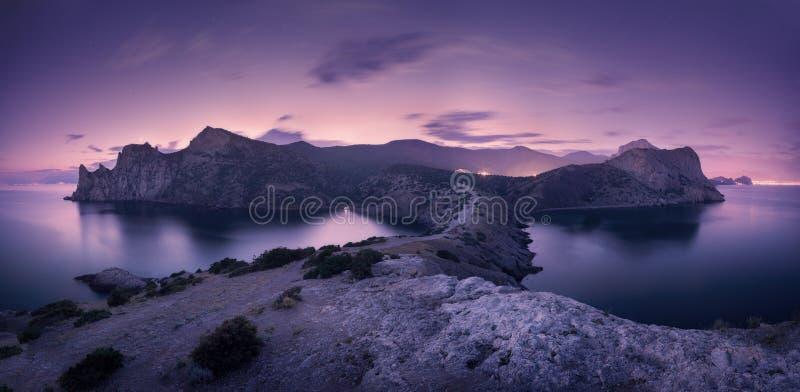 与山、海和满天星斗的天空的美好的夜风景 库存照片