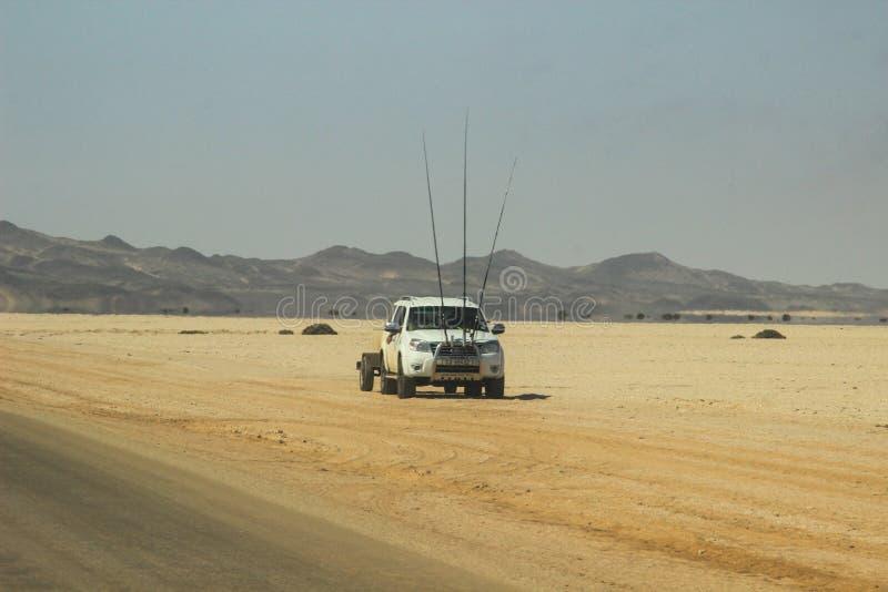 与山、路和汽车的沙漠风景有在纳米比亚的南部的钓鱼竿的 旱季,干燥植被是natu 免版税库存照片