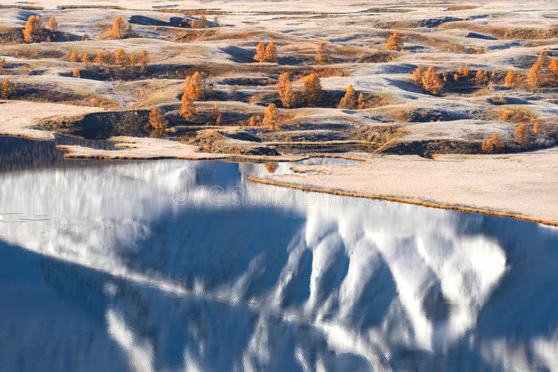 与山、雪&黄色落叶松属和美丽的湖的明亮的秋天风景有反射的 库存照片